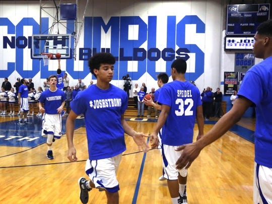 Trey Vincent and his Columbus North teammates wear #Joshstrong No. 32 Josh Speidel shirts during the warmups before the Bulldogs' game against Hamilton Southeastern at home on Tuesday, Feb. 3, 2015. Speidel, the team's star player, was critically injured in a two-car accident on U.S. 31 on Sunday night and is in critical but stable condition at Methodist Hospital in Indianapolis. Columbus North lost the game to the Royals by a score of 64-49.