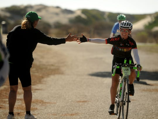 Volunteer Mary Gonser, left, high-fives Megan MacArthur at San Buenaventura State Beach, Friday's destination for the Arthritis Foundation's California Coast Classic Bike Tour.