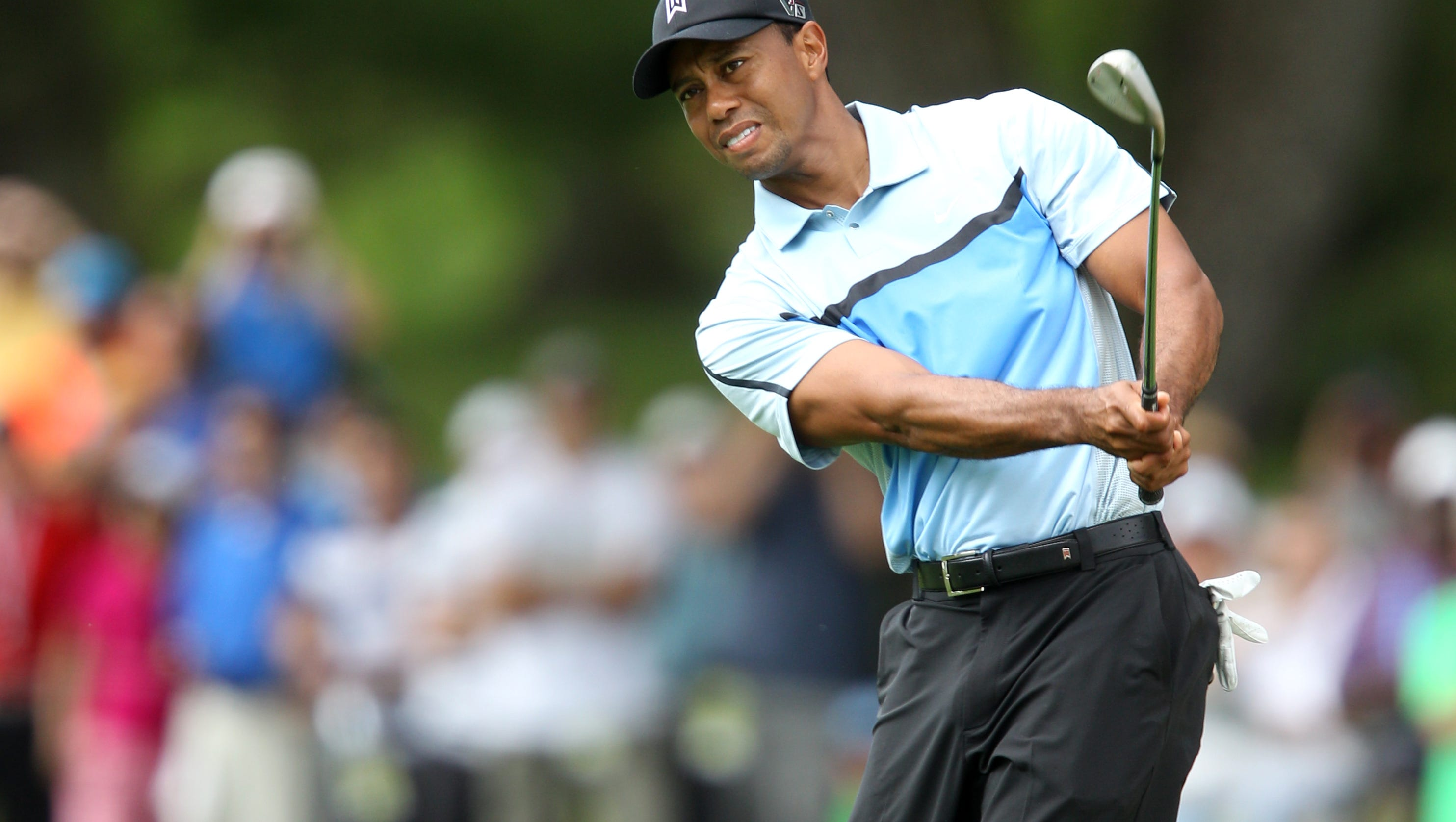 Tiger Woods watches his chip shot to 17 during the first round of the 95th PGA Championship at Oak Hill in Pittsford, NY August 8, 2013. He made birdie on 17.