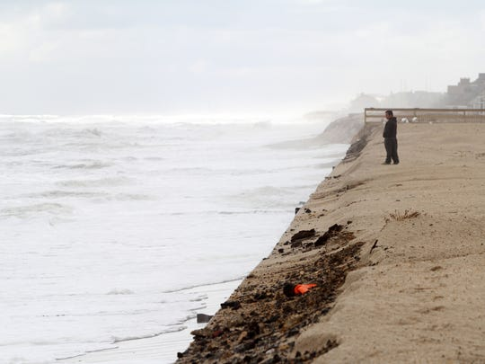 A man looks towards the Atlantic Ocean as it continues to batter the exposed sea wall, Monday, October 5, 2015, in Mantoloking.