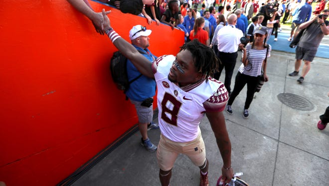 FSU's Nyqwan Murray high-fives fans after the Seminoles 38-22 win over Florida at Ben Hill Griffin Stadium in Gainesville on Saturday, Nov. 25, 2017.