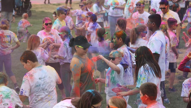 """Contestants participate in a """"color war"""" at the Desert Color Dash in Hafen Park in Mesquite on March 10, 2018."""