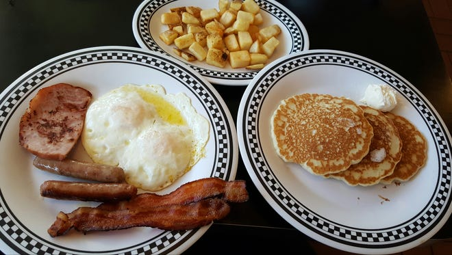 The Aggie Sampler from Pancake Alley comes with pancakes, fried potatoes, two eggs and bacon, sausage links and grilled ham, and a choice of pancakes, toast or a muffin.