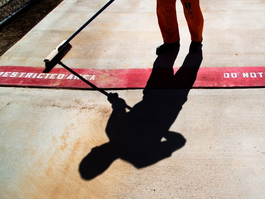 An inmate sweeps a sidewalk with a marker indicating