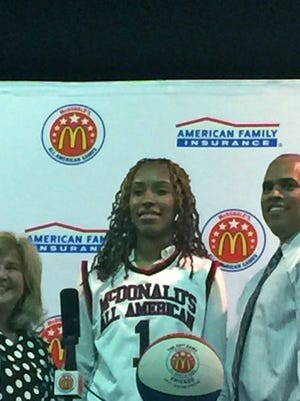 Queen of Peace senior Raven Farley-Clark, center, received her McDonald's All-American jersey at a ceremony at school Thursday morning. Farley-Clark was joined by two area McDonald franchise owners.