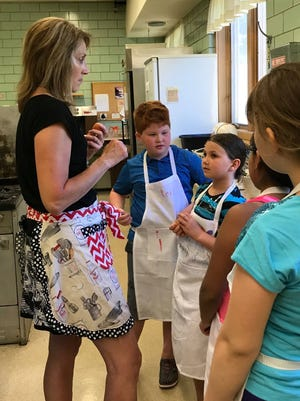Budding Chefs owner Deb Johnson of De Pere works with a group of children in one of her classes.