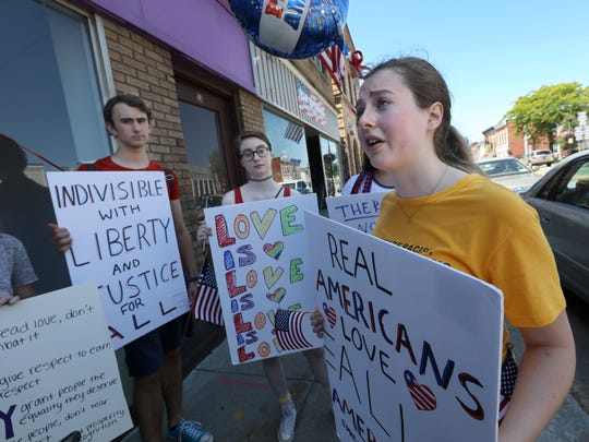 Katie Fornof, 16, right, with friends Noa Shapiro, 17, center, and Luke Stowell, 16, left, all of Webster, protest outside the newly opened Trump's Team Deplorable Community Activity Center, on Main Street in Webster on Wednesday, July 4, 2018.