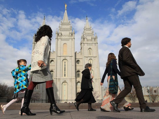 "In this April 5, 2014 file photo, people walk past the Salt Lake Temple in Salt Lake City. On Tuesday, Jan. 27, 2015, Mormon leaders made a national appeal for what they called a ""balanced approach"" in the clash between gay rights and religious freedom, promising to support some housing and job protections for gays if they back some exemptions for religious objectors to same-sex marriage."
