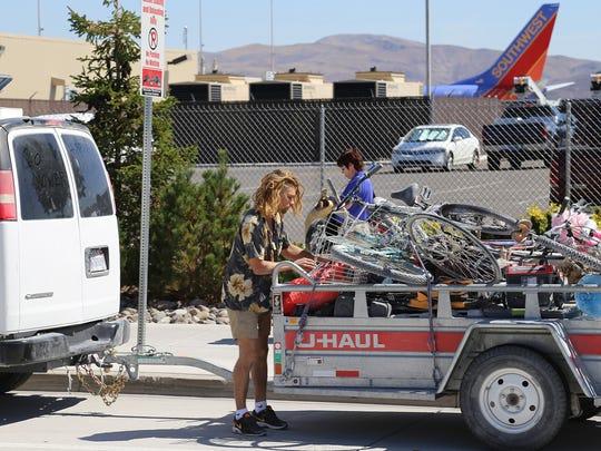 A Burner hauls in several bikes at the Reno-Tahoe International Airport after Burning Man.