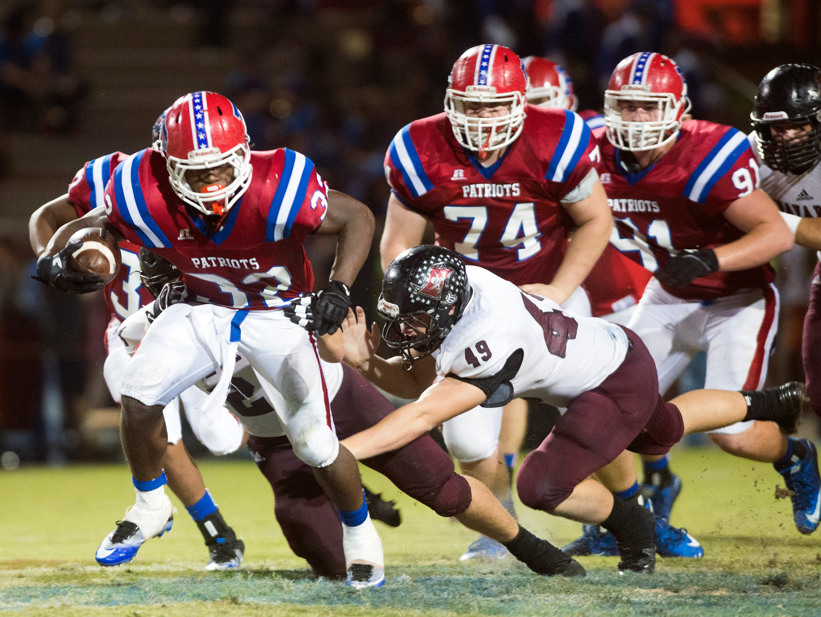 Pace High School running back Anthony Johnson, Jr. (No. 32) gives Navarre High School defensive end, Ryan Struck, (No. 49), the slip to gain extra yards during Friday night's District 2-6A matchup.