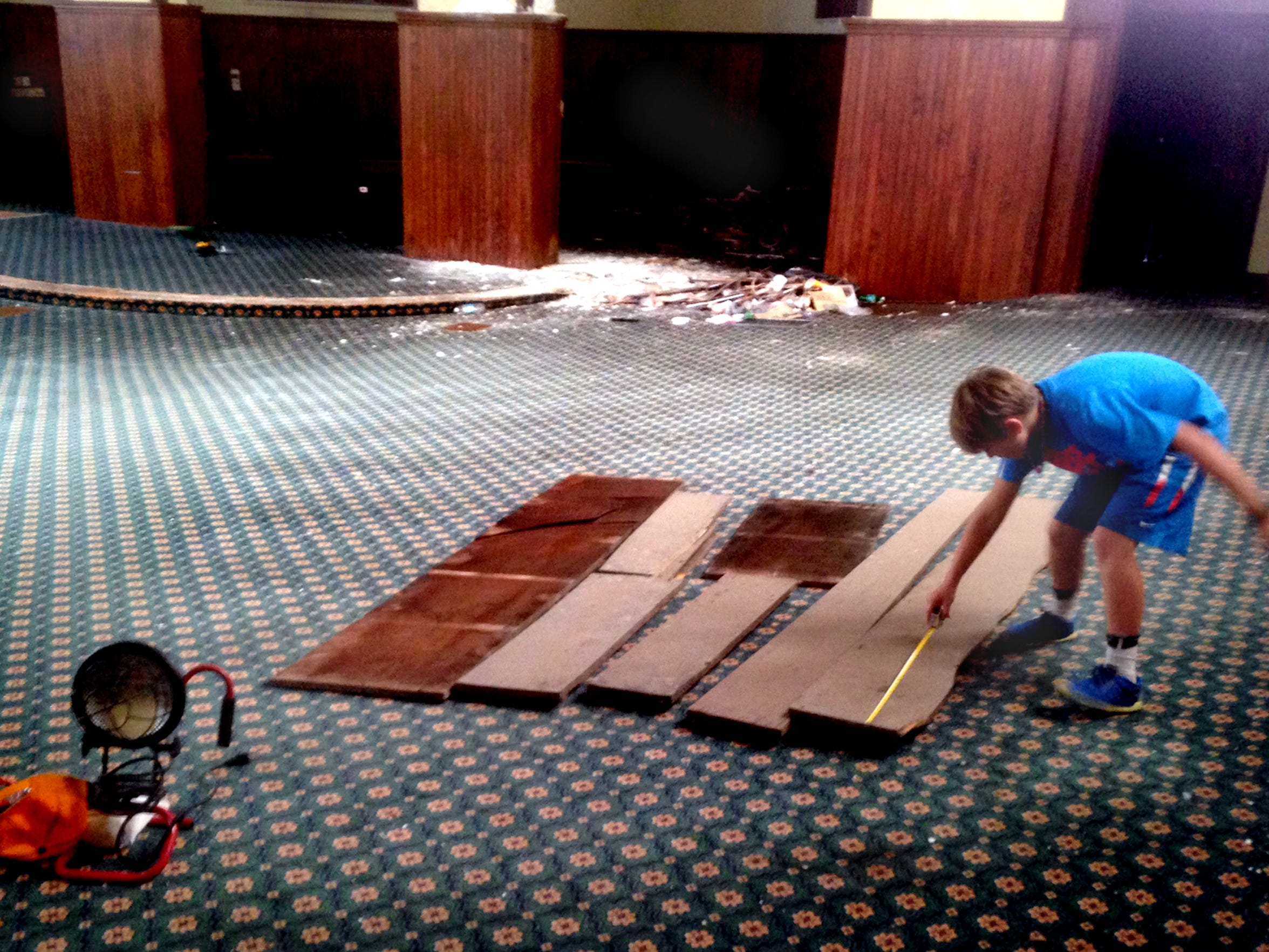 Andrew Gaines, 10, measures boards on the former sanctuary floor of First United Methodist Church. He joined family members and others from the congregation to recover boards from the bell tower of a former church building that dates back to 1888. The congregation relocated to West Thompson Lane by the Siegel School in 2003.