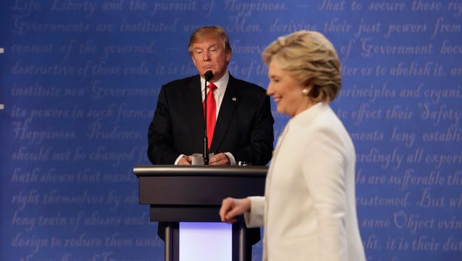 Republican presidential nominee Donald Trump waits behind his podium as Democratic presidential nominee Hillary Clinton makes her way off the stage following the third presidential debate in Las Vegas on Wednesday.