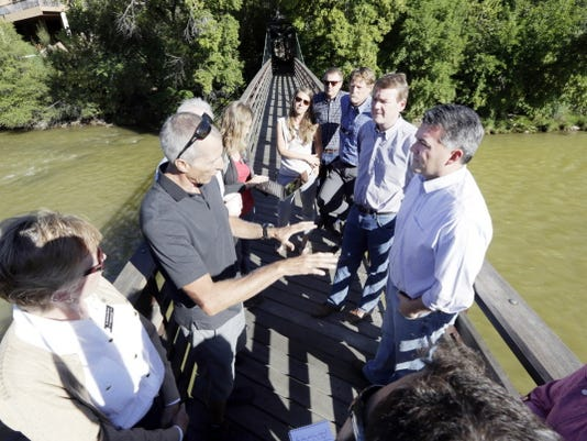 Andy Corra, left, co-owner of 4 Corners Riversports in Durango, Colo., talks with Colorado U.S. Sens., Cory Gardner, front right, and Michael Bennet, middle right, on a bridge over the Animas River, Sunday, in Durango.