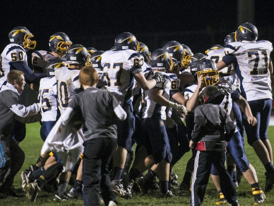 Elco players mob kicker Dane Miller after his extra point put the finishing touches on the Raiders' wild 40-39 overtime victory over Annville-Cleona on Thursday night.
