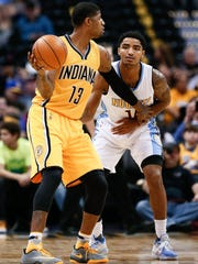 Indiana Pacers forward Paul George (13) controls the ball against Denver Nuggets guard Gary Harris (14) in the third quarter at the Pepsi Center.
