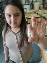 Alicia Sanchez, 12, holds up a plastic baby that will