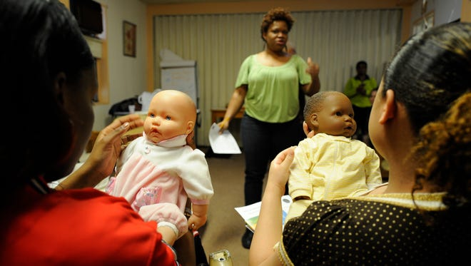 In this 2008 photo in New York City, Maybeli Mercado, right, and Shaquasia Massey, left,  (who had just given birth) hold toy babies and  listen to Baby Basics Health Educator Evelyn Alverez. The author of What to Expect When You're Expecting has started a foundation and written a pregnancy book aimed at at-risk, low-income moms who can't afford or can't read her famous book.