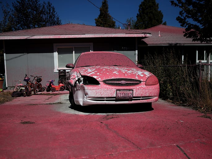 Foscheck fire retardant dropped from an airplane covers a car in front of a home in Weed, California on Sept. 16, 2014, after a wildfire ripped through the town burning hundreds of structures including the high school and lumber mill.