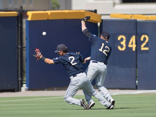 Tony Renda (2)'s pop fly drops in for an in-the-park home run as BayBears players Ildemaro Vargas (2) and Cody Regis (12) collide during the Mobile BayBears vs. Blue Wahoos baseball game at Blue Wahoos Stadium in Pensacola, FL on Sunday, June 17, 2016.  The Blue Wahoos wore the throw-back uniforms of the Pensacola Pelicans.