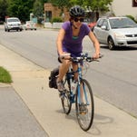 """Lauren Kanner uses the sidewalk for her bike route along Charlotte Street because of heavy traffic. """"There's really not a lot of shoulder room,"""" she said. City government proposes improving sidewalks along the street and directing bicyclists to nearby streets."""