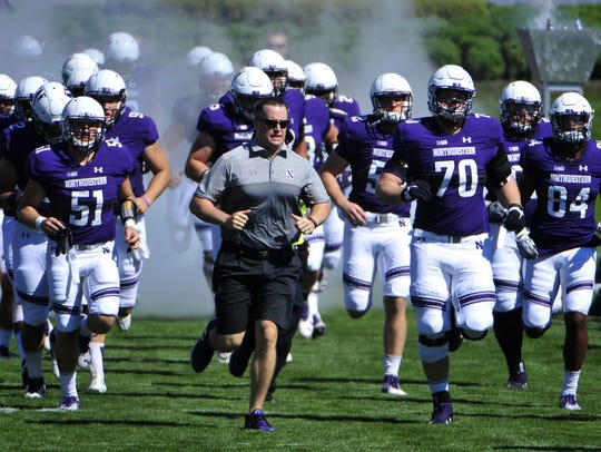 Head coach Pat Fitzgerald leads his Northwestern team onto the field.