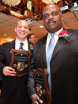Former New York State Police Troopers Seamus Lyons, left, and Noel Nelson, right, hold plaques during awards ceremonies at the Haverstraw Elks Club in 2012. The two filed a federal civil rights lawsuit against the department onTuesday, May 12, 2015, claiming discrimination and that they were scapegoated for missing evidence from Troop K barracks in Hawthorne.