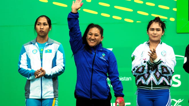 "Weightlifter Jacinta ""Ja"" Sumagaysay waves to the crowd as she is introduced along with other weightlifters in the 58 kilogram class during the Asian Indoor and Martial Arts Games held September in Turkmenistan. Sumagaysay set three Guam national records during those Games."