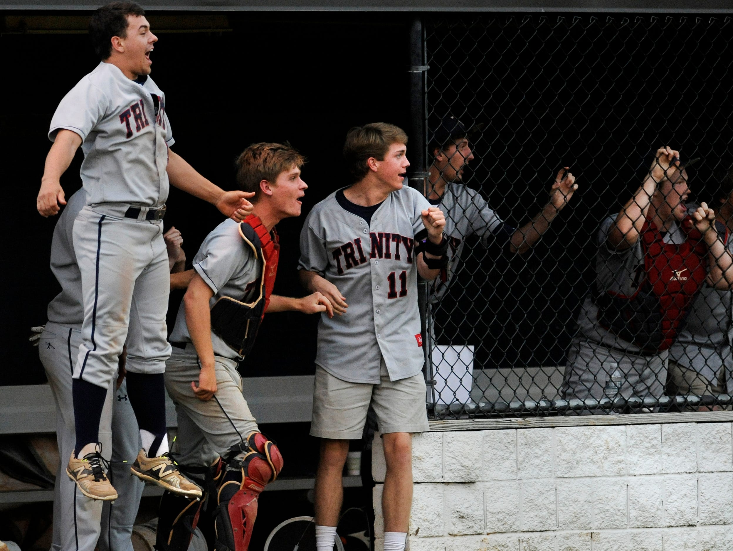 The Trinity dugout celebrates sixth inning runs in the first game of a double header against St. James on the St. James campus in Montgomery, Ala., on Friday April 24, 2015.