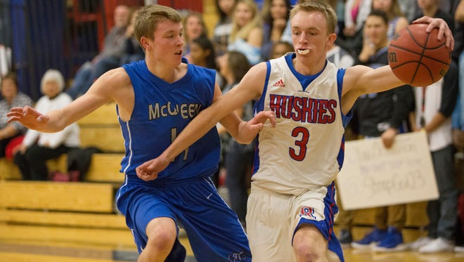 Reno's Drew Rippingham dribbles as McQueen's Zach Stallings defends during their basketball game played on Tuesday,  at Reno.