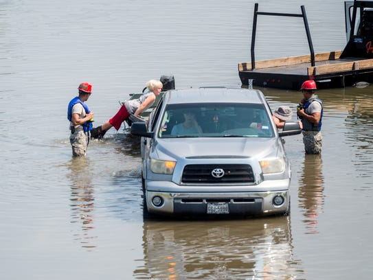 A family is rescued from their car Friday in Port Arthur,