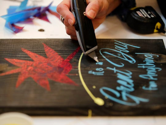 Linda Weidert helps her son, Henry, cut out pieces of a stencil that he designed while working on an art project at Crafty Wood Maker Studio in Appleton.
