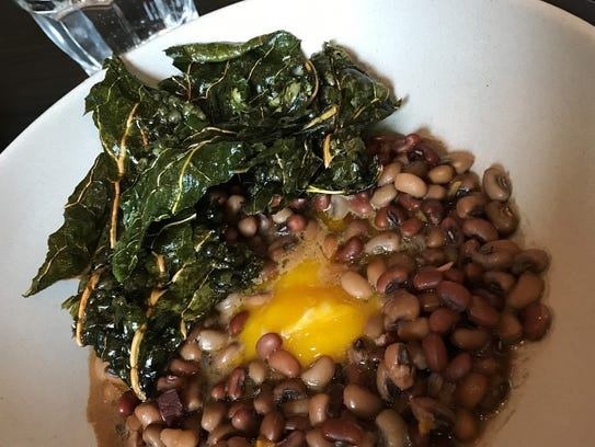 Black-eyed peas with egg yolk and crispy greens at