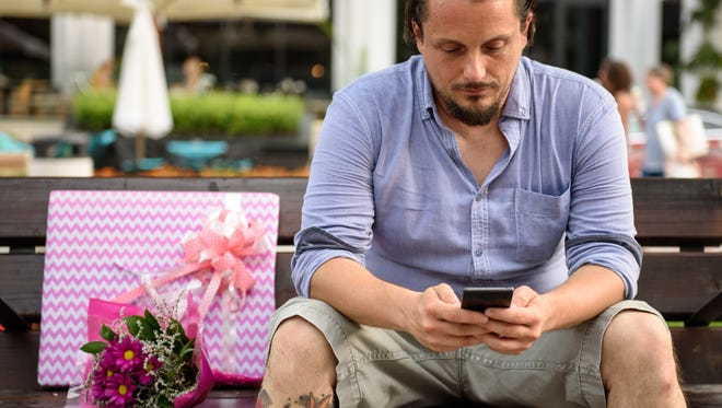 White Caucasian man with tattooed leg, sitting on a bench, using his mobile device. A pink wrapped box and flowers next to him.
