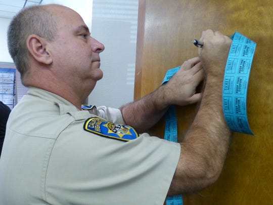 California Highway Patrol Capt. George Peck fills out his raffle tickets at a fundraiser for truck driver Jeff Smith.