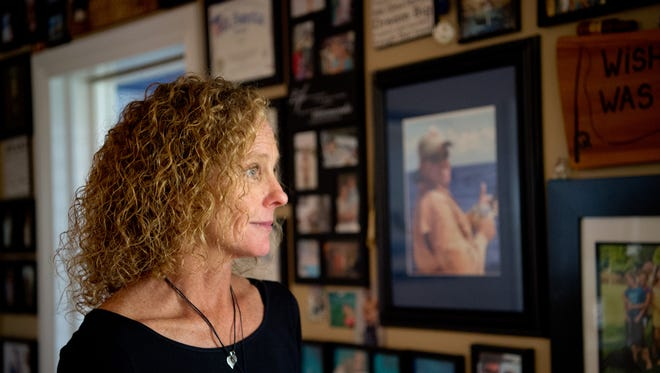 Kristen Simpson, photographed near a wall of family photos at her longtime Vero Beach home Sunday, April 30, 2017, lost her husband, Brian Simpson, when he was shot inside the house during a burglary in 2011. The convicted murderer, Henry Jones Jr., may be in court again after an appeals court ordered a new trial.