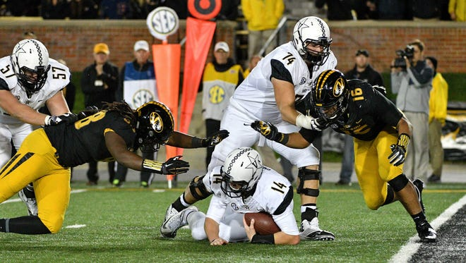 Vanderbilt quarterback Kyle Shurmur (14) is sacked by Missouri defensive linemen Marcell Frazier (16) and Nate Howard (88) in the second half Saturday.