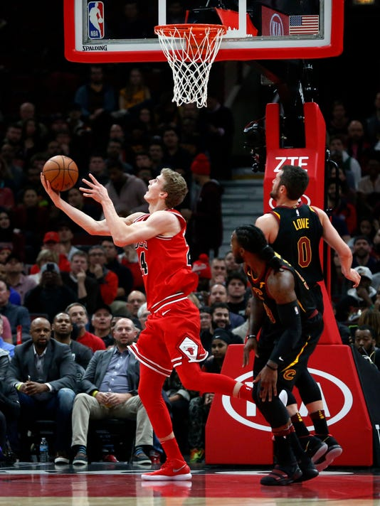 Chicago Bulls' Lauri Markkanen, left, scores on a reverse layup past Cleveland Cavaliers' Kevin Love (0) and Jae Crowder during the first half of an NBA basketball game Monday, Dec. 4, 2017, in Chicago. (AP Photo/Charles Rex Arbogast)