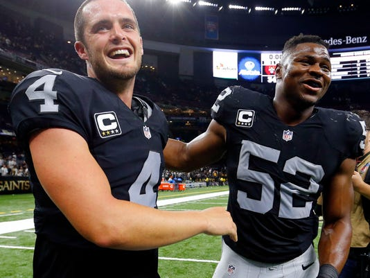 Oakland Raiders quarterback Derek Carr (4) celebrates with defensive end Khalil Mack (52) after an NFL football game against the New Orleans Saints in New Orleans, Sunday, Sept. 11, 2016. The Raiders won 25-34. (AP Photo/Butch Dill)