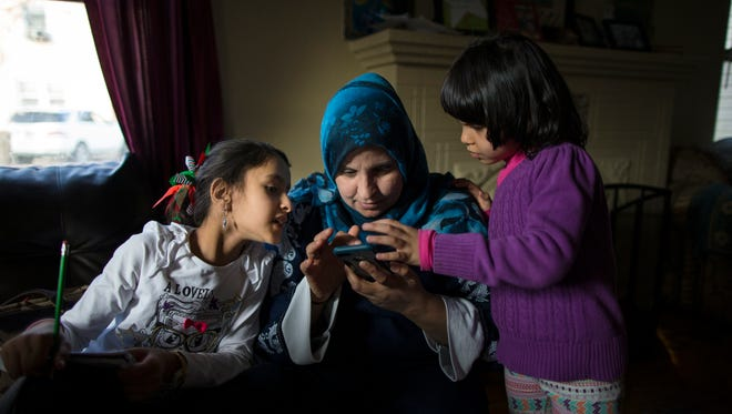 Ahlam Alhamoud, 36, swipes through photos taken on an iPhone by her daughter Rimas, 5, (right) while Zina, 7, peeks over from her homework at their home in Cincinnati, on Monday, Jan. 30, 2017. The Alhamoud family moved to Cincinnati as refugees from Syria in November 2015.