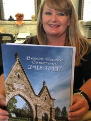 Beech Grove Cemetery office manager Tina Sulfridge displays the new book about the cemetery.