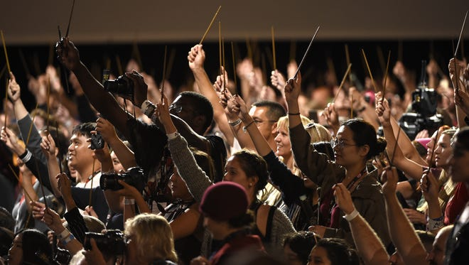 """The audience waves their wands at the """"Fantastic Beasts and Where to Find Them"""" panel on day 3 of Comic-Con International on Saturday, July 23, 2016, in San Diego. (Photo by Chris Pizzello/Invision/AP)"""