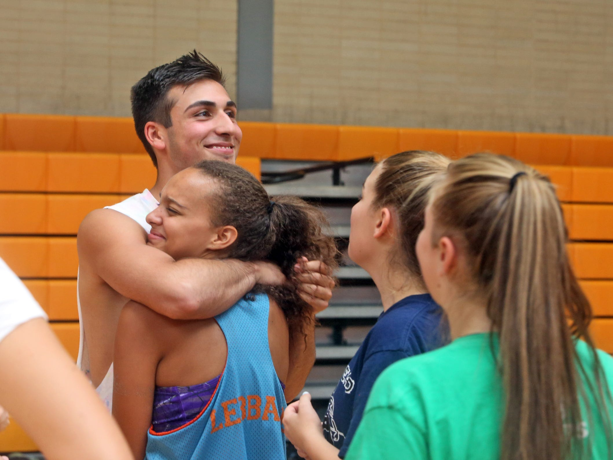 Andreo Otiniano, a senior at Mamaroneck High School, and a member of the girls volleyball team, hugs teammate Amanda Gutierreza during practice Sept. 16, 2015. Otiniano played with the team as a sophomore, and still practices with the team and is on the roster, but present Section 1 rules do not allow him to play in matches.