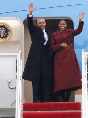 Former President Barack Obama and his wife Michelle wave as they board an Air force jet to depart Andrews Air Force base in Maryland and head to Palm Springs on Friday, Jan. 20, 2017.