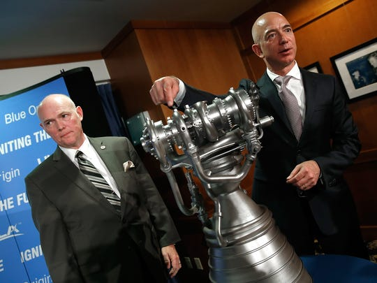 Amazon and Blue Origin founder Jeff Bezos with a small replica of the company's BE-4 rocket engine. In background is Tory Bruno, president and CEO of United Launch Alliance.