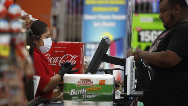 Amid social distancing during the Covid-19 outbreak, a cashier wears a mask while working behind a clear barrier between her and a customer at El Rancho grocery store in Dallas, Thursday, March 26, 2020. For most people, the new coronavirus causes mild or moderate symptoms, such as fever and cough that clear up in two to three weeks. For some, especially older adults and people with existing health problems, it can cause more severe illness, including pneumonia and death.