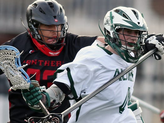 Polytech's Marcus Davis (left) defends against Archmere's Nate Beatson in Archmere's 9-8 win Wednesday, April 2, 2014 at Archmere Academy.