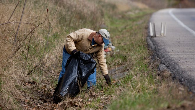 Jeff Tallmadge, of Port Huron, picks up trash along with members of Boy Scout Troop 168 Saturday in the Port Huron State Game Area on Abbottsford Road in Clyde Township.