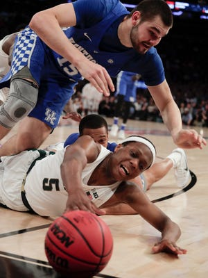 Michigan State guard Cassius Winston (5) and Kentucky forward Isaac Humphries (15) scramble for a loose ball during the second half of MSU's 69-48 loss to Kentucky Tuesday in New York.