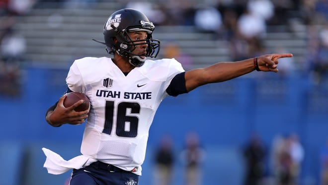 Utah State Aggies quarterback Chuckie Keeton (16) points to his teammates as he elects to run against the San Jose State Spartans during the first quarter at Spartan Stadium.