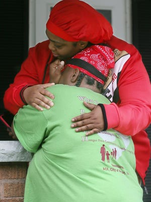 Jhovonne Taylor, back to camera, gets a hug from a neighbor Friday, the morning after Taylor's daughter Ty'Leia Junius, 14, was killed on Brighton Drive in Akron.